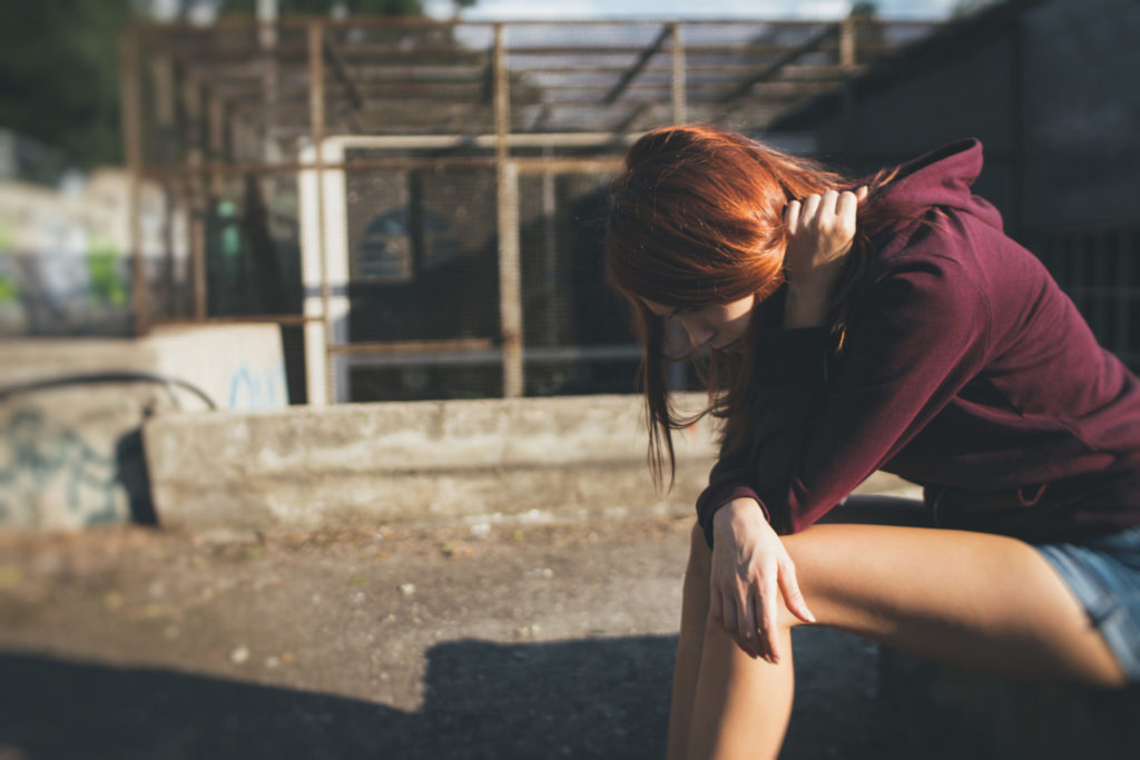 Depressed teen girl with red hair looks down