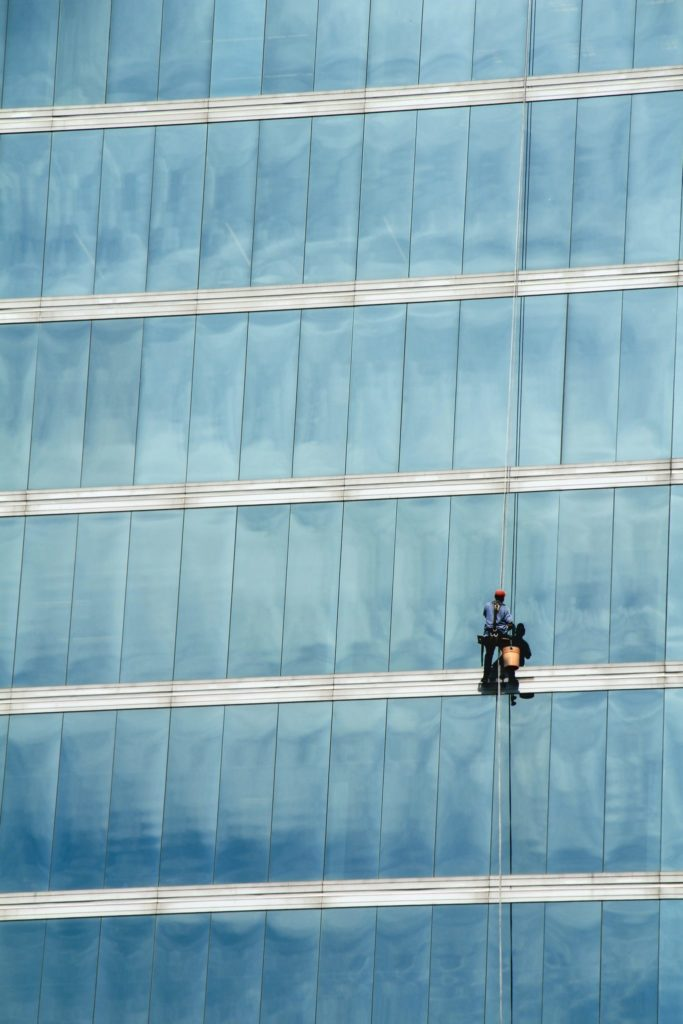 Image of a window washer working on a large glass building