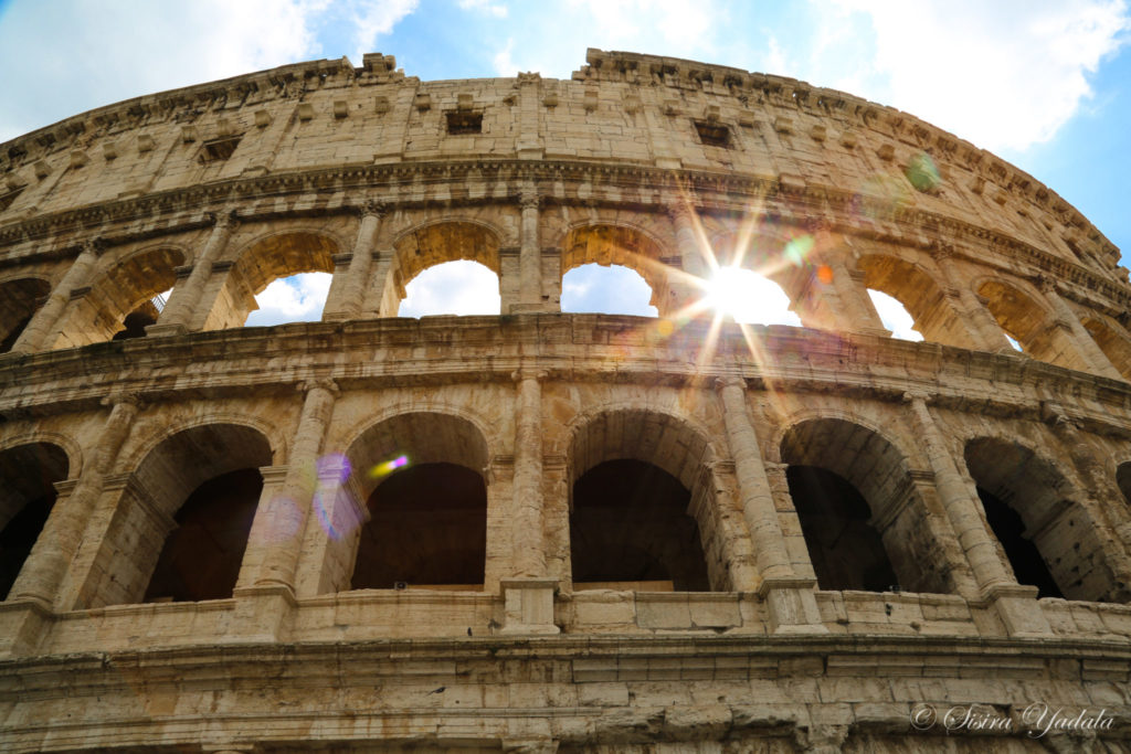 Photo of Roman Colosseum with sunlight streaming through an opening
