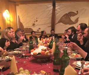 Image of a large group of people eating at a table covered with fruits, cheeses, and various bottles.
