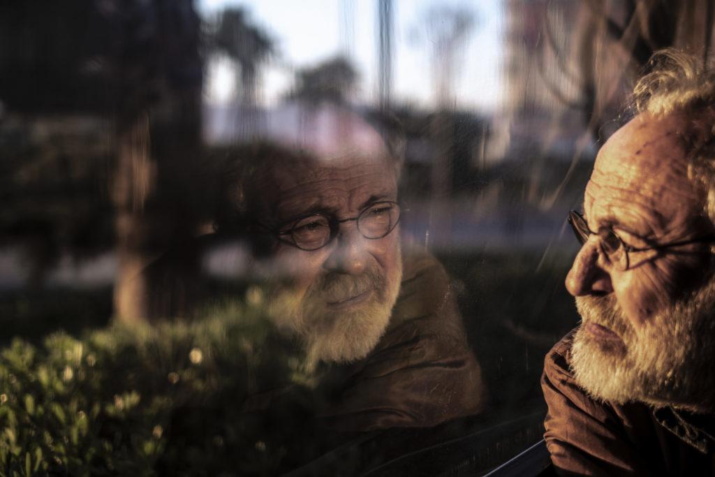 Elderly man reflected in a window